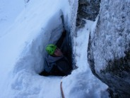 Squeezing out the tunnel, at the end of Pitch 2, West Chimney, Church Door Buttress.