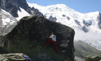 Climbing the Slab boulder with the Dome du Gouter in the background.