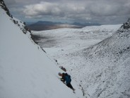 Snow field banks out below rock wall