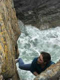 Katie soloing Fishermans Friend above a wild sea