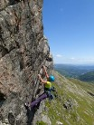Climber on Crow's Nest Direct, Gimmer Crag on a sunny summer day