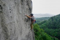 Ed reaching for the crux hold whilst trying to get out of the impeding rain