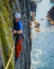 Climber approaching the belay on  pitch 1 of Lighthouse Arete, Castell Helen