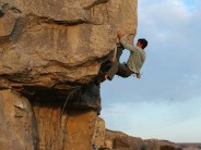 Andy Lamont getting out of the crux of Revhead's High-Roller, 7b, Winspit