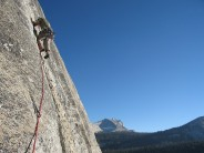 Leaving belay on third pitch of West Crack. Cathedral Peak in the background.